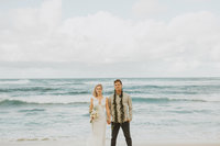 bride and groom standing in front of ocean