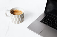 kaboompics_Cup of coffee & Macbook laptop on white marble