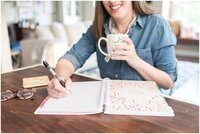Female business owner in chambray shirt with cup of tea and an open notebook