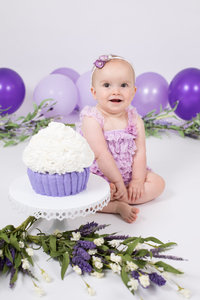 Shades of lavender balloons and floral decor for cake smash
