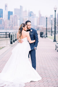 Bride and groom in Liberty State Park with NYC skyline at Liberty House wedding captured by Best Wedding Photographer in NJ Myra Roman Photography
