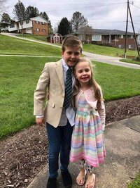 Little boy and girl posing in Sunday best outfits