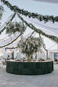 Round bar at tented wedding with tree centerpiece and floral chandeliers