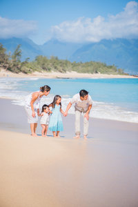family plays in the water at baldwin beach for their maui photo session.