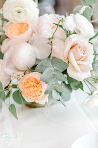 Detail shot of a centerpiece of peach and white flowers.