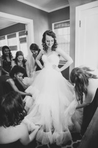 Bride getting ready with bridesmaids fluffing wedding gown