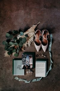 Bride's wedding shoes, invitation, and flowers styled on industrial cement floor