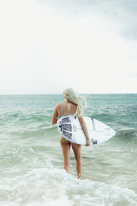 woman looking at ocean while holding surf board