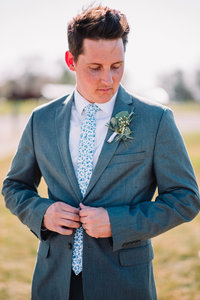 groom buttoning jacket wedding idaho