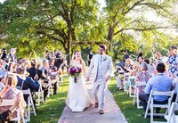 Bride and groom walk up aisle at cw hill country ranch