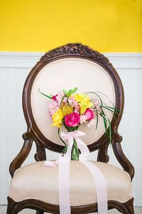 A colorful bouquet sits on a vintage chair.