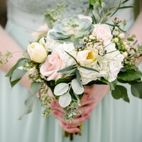 Close up of a bridesmaid in a sea green dress holding beachy floral bouquet