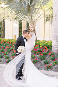 Bride and groom kissing as her veil flows