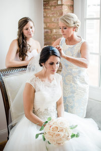 Bride with mother and bridesmaid getting ready for wedding day