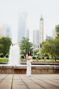 pregnant mom holding belly in front of fountain charlotte skyline