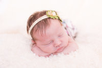 Newborn baby girl sleeps atop soft fuzzy white blanket during newborn photography session