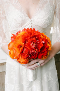Bride detail with orange bouquet.