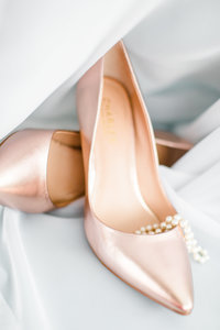 blush shiny bridal shoes with bridal pearl necklace  detail shot