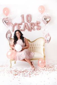 Kiamarie Stone celebrates 10 years in business on white settee with ballons