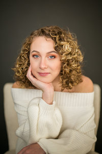 Teen girl with blonde curly hair poses for portrait in white sweater