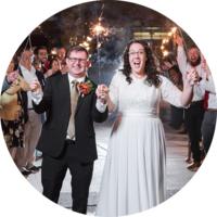 Bride and groom smile together during sparkler exit during Logan wedding
