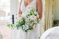 Bride holding bouquet by Bleedfoot Florals in the bridal suite at Harmony Meadows