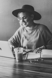 girl in hat smiling at computer
