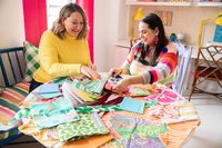 Two women look through colorful swatches and fabrics.