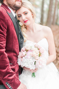 red lipstick on bride with groom wearing a suede maroon jacket