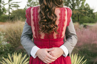 Man embraces fiance around the waist while her dark curly hair covers the back of her red lace dress during  sunset engagement session at Alt Park