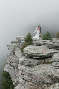 Photography of a couple from a distance at Pilot  Mountain standing on a rock with fog in the background