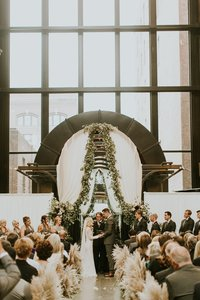 Bride and Groom say I do under arch draped with fabric and garland in Seattle's Court in the Square