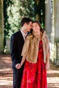 •	Engagement photo of man in dark blue suit, holding the hand of his fiancé in a red dress and fur coat at Harkness Memorial State Park