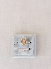 Close up of grey ring box holding teardrop yellow diamond ring with little round diamonds around it with round diamonds all around the band. Below is the platinum wedding band with round diamonds inside wrapping all the way around. Photographed by Wedding Photographers in Charleston Amy Mulder Photography.