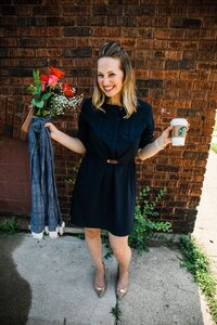woman smiling at camera holding starbucks cup in one hand and roses and a  blue scarf in the other in front of a brick wall