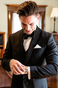 Groom putting on his watch in the library at Elsie Perrin Williams Estate