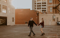 Couple holding hands and walking in a parking garage in the city