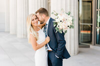 Bride and groom posing in front of white columns in Alabama