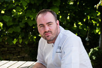 close up relaxed headshot of Nick Deverell-Smith who is head chef at the Churchill Arms in Paxford.  He's dressed in his chef whites and looking at the camera.  The photo is taken outside with a green hedge in the background.