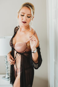 boudoir picture of woman in the lingerie standing and holding her bra