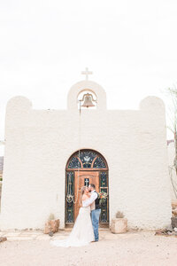 A bride and groom facing one another infront of an old mission church in Lajitas, Texas.
