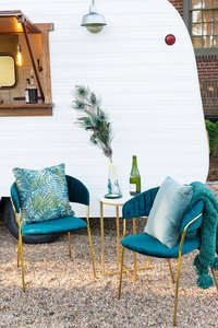 Two teal chairs in front of a camper.