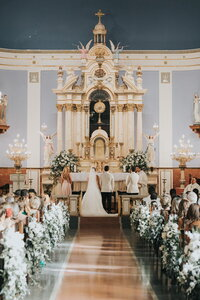 Bride and groom on altar of St. Mary's Church with floral aisle decor