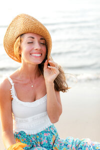 Portrait of a girl sitting on the beach with a floppy beach hat. She is smiling up to the sky.
