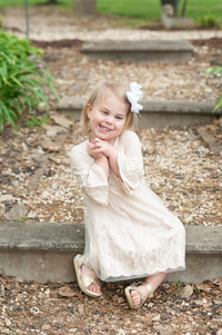 Adorable girl sitting on steps in Bowling Green, KY garden
