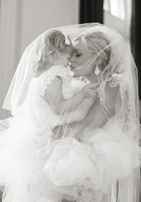 A bride and flower-girl are kissing under the brides vail.