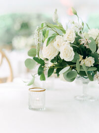gold rimmed candle votive with white rose flower centerpiece for a wedding reception.