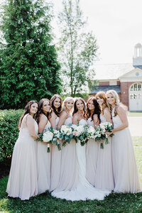 bridesmaids huging eachother looking into the camera