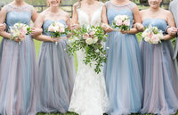 Bride and her bridesmaids link arms and hold their bouquets