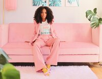 african american woman in pink suit on a pink couch posing for the camera